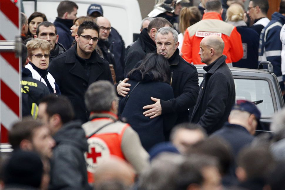 French former Youth and Associations Junior minister Jeannette Bougrab (C) is comforted by an unidentified person outside of