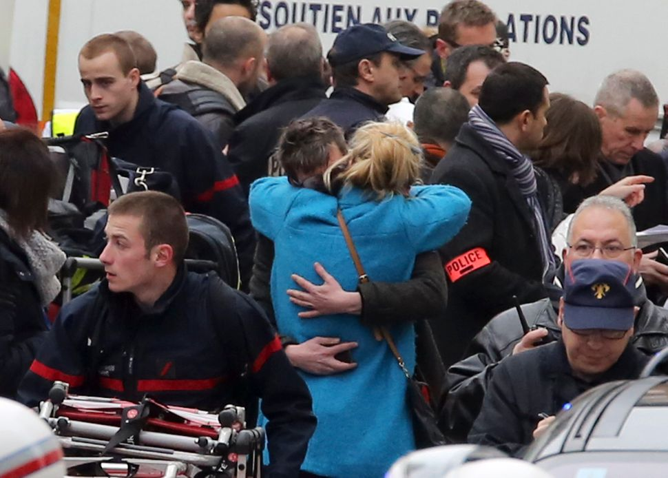 People hug each other outside the French satirical newspaper Charlie Hebdo's office, in Paris, Wednesday, Jan. 7, 2015.