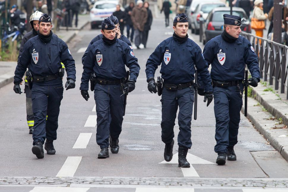 Police officers take security measures near the offices of the French satirical newspaper Charlie Hebdo in Paris on January