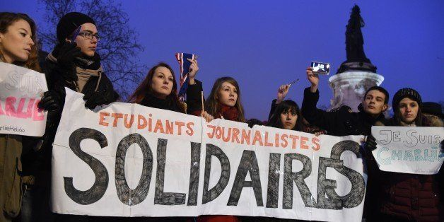 Journalism students hold a banner reading in French: 'Journalism students : Solidarity' as they raise pens during a gathering