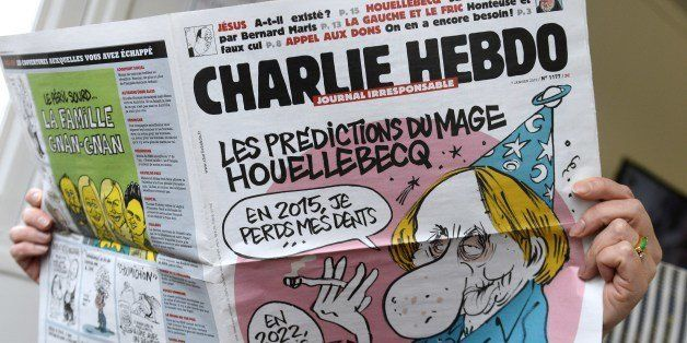 A person reads the latest issue of the French satirical newspaper Charlie Hebdo in Paris on January 7, 2015, after gunmen arm