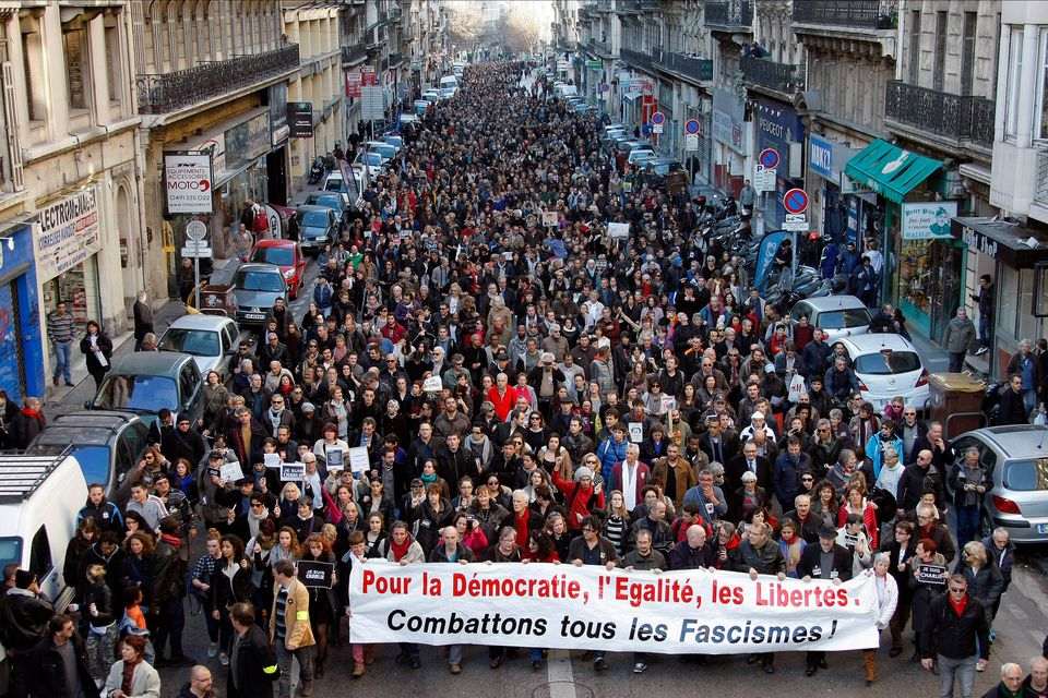 "Demonstrators hold a banner reading ""For democracy, for equality, for freedoms. Let us fight all fascism!"" during a demonstra"
