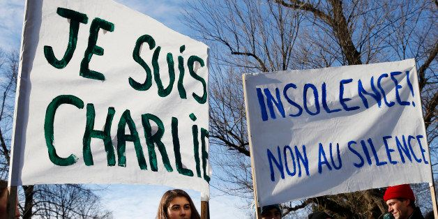 BOSTON - JANUARY 11: Lucy Brown, 16, of Cumberland, ME, holds a 'Je Suis Charlie' sign as her brother Nico, 14, and father Ma