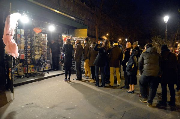 Customers wait in line at Pigalle newstand, where the new edition of Charlie Hebdo magazine is being sold on January 14, 2014
