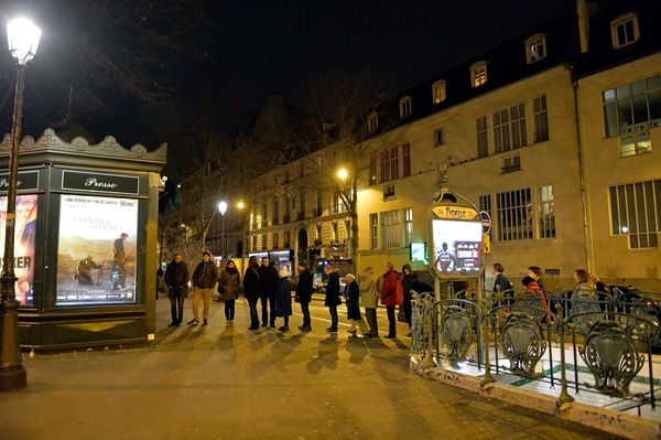 Customers wait in line at Pigalle newsstand, where the new edition of Charlie Hebdo magazine is being sold on January 14, 201
