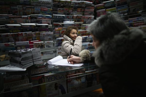 A woman signs a waiting list to purchase a copy of the latest edition of Charlie Hebdo magazine at a news kiosk on January 14