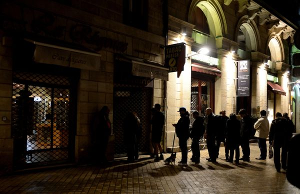 People wait outside a newsagents in Bordeaux on January 14, 2015 as the latest edition of French satirical magazine Charlie H