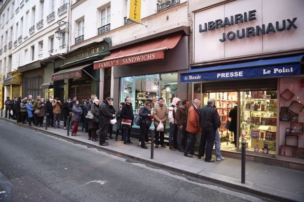 People wait outside a newsagents in Paris on January 14, 2015 as the latest edition of French satirical magazine Charlie Hebd