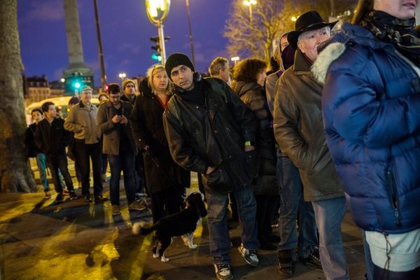 Members of the public queue at a newspaper kiosk, where copies of the latest edition of Charlie Hebdo magazine are being sol