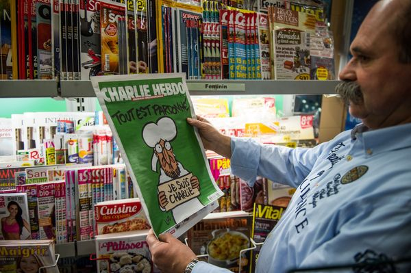A man reads the latest edition of French satirical weekly Charlie Hebdo at a newsagents in Dunkirk on January 14, 2015 as the