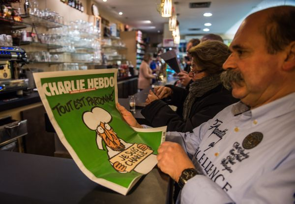 A man reads the latest edition of French satirical weekly Charlie Hebdo in Dunkirk on January 14, 2015 as the latest edition