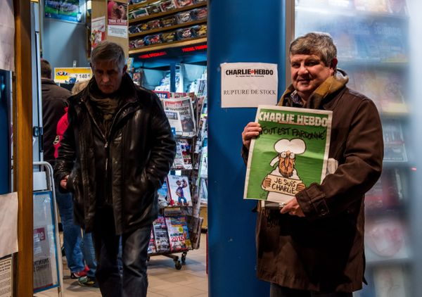 A sign which translates as 'Charlie Hebdo - Sold Out'  is displayed as a customer holds a copy of the magazine outside a news