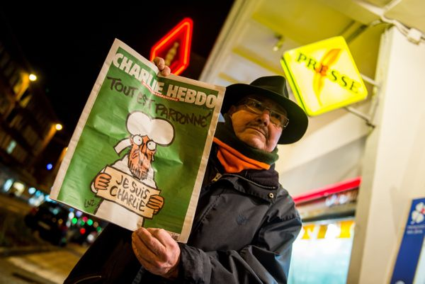 A customer holds a copy of Charlie Hebdo outside a newsagents in Dunkirk on January 14, 2015 as the latest edition of French