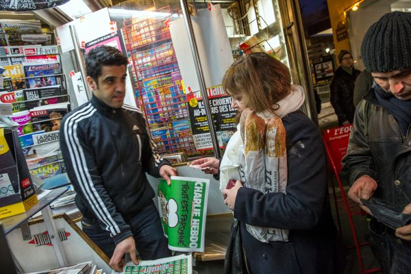 A woman buys a copy of the latest edition of Charlie Hebdo magazine at a newspaper kiosk on January 14, 2015 in Paris, France