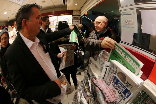 In this photo made with a fish-eye lens, people pick up copies of Charlie Hebdo newspaper at a newsstand in Rennes, western F