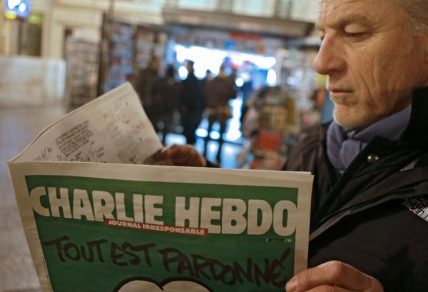 Jean Paul Bierlein reads the latest issue of Charlie Hebdo outside a newsstand in Nice, southeastern France, Wednesday, Jan.