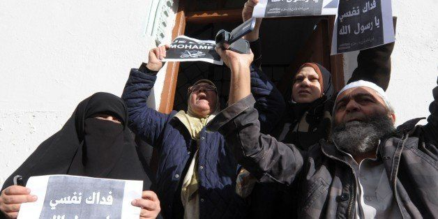 Algerian protestors hold up placards during a demonstration against French satirical weekly Charlie Hebdo for publishing a ca