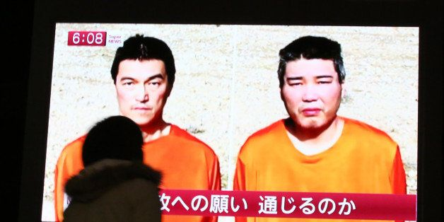 A passer-by watches a TV news program reporting two Japanese hostages, Kenji Goto, left, and Haruna Yukawa, held by the Islam