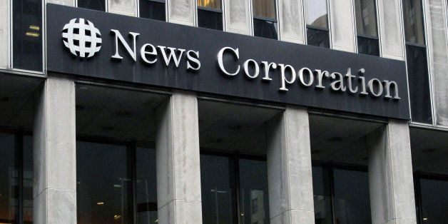 FILE - In this Oct. 12, 2011 file photo, people walk in front of the News Corporation building in New York. News Corp. said T