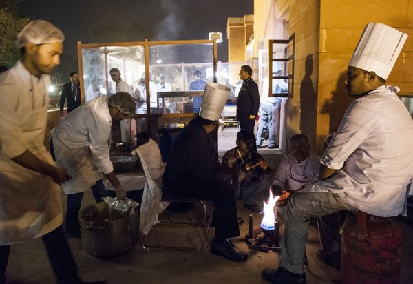 Kitchen staff warm up by a fire as they prepare a State Dinner in honor of US President Barack Obama at Rashtrapati Bhawan, t