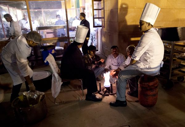 Kitchen workers gather round a warm flame outside the Rashtrapati Bhavan, the presidential palace, as US President Barack Oba