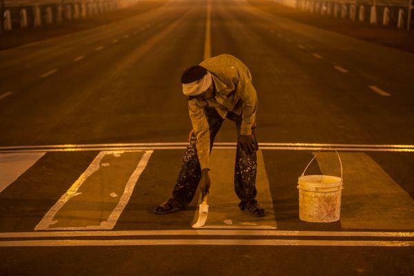 A worker applies a fresh coat of paint to the street lines as India prepares for the Republic Day celebrations in New Delhi,