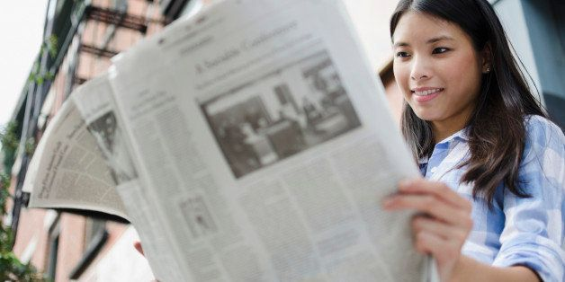 Asian woman reading newspaper