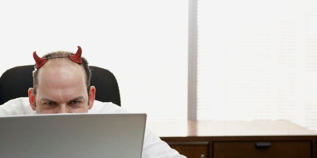 Mature businessman with devil horns using laptop in office