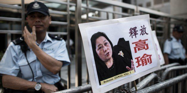 A policeman stands guard outside the China liaison office next to a placard showing a portrait of Chinese journalist Gao Yu l
