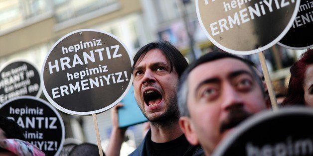 People hold placard reading ' we all are Hrant, We all are Armenians'  as they shout slogans in front of Armenian newspaper '