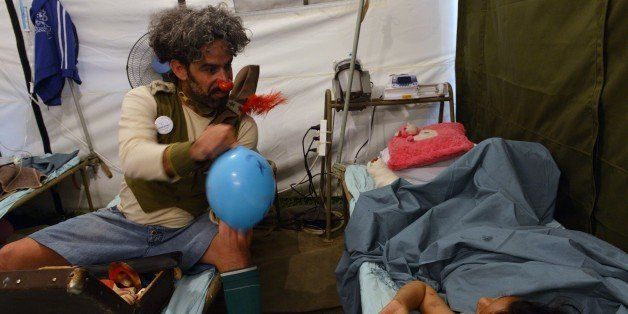 An Israeli medical clown entertains a Nepalese earthquake victim during a visit to a makeshift army camp in Kathmandu on May