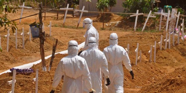 FILE- In this file photo dated Wednesday, March 11, 2015, health workers walk inside a new graveyard for Ebola victims, on th