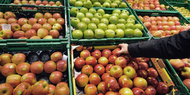 A woman shops apples in the fruits produce section of a Carrefour supermarket on March 15, 2012 in the French northern city o