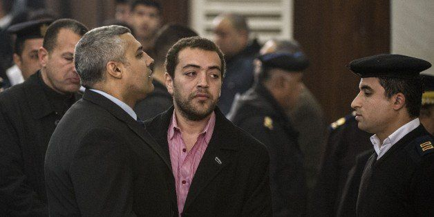 Al-Jazeera's Egyptian producer Baher Mohamed (C) and Egyptian-Canadian reporter Mohamed Fadel Fahmy (L) attend their trial at