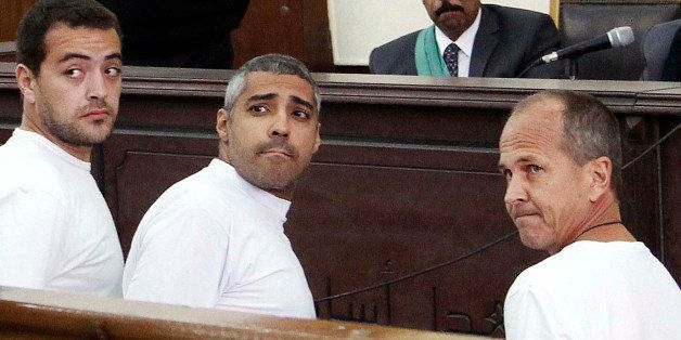 FILE - In this  Monday, March 31, 2014 file photo, Al-Jazeera English producer Baher Mohamed, left, Canadian-Egyptian acting