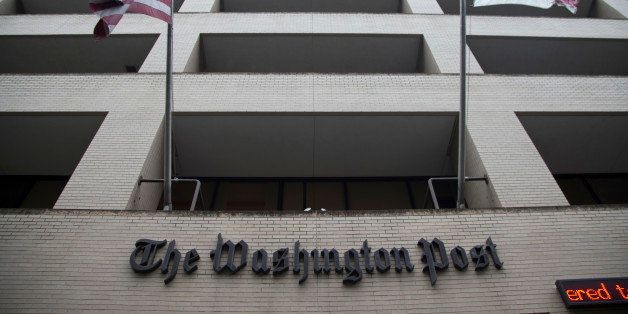 FILE - In this Aug. 6, 2013, file photo, an American flag, left, and a District of Columbia fly outside The Washington Post b