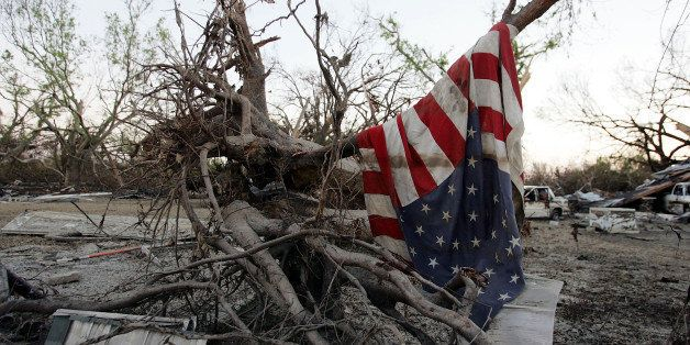 PORT SULPHUR, LA - SEPTEMBER 11:  An American flag hangs in a pile of debris after Hurricane Katrina passed through September