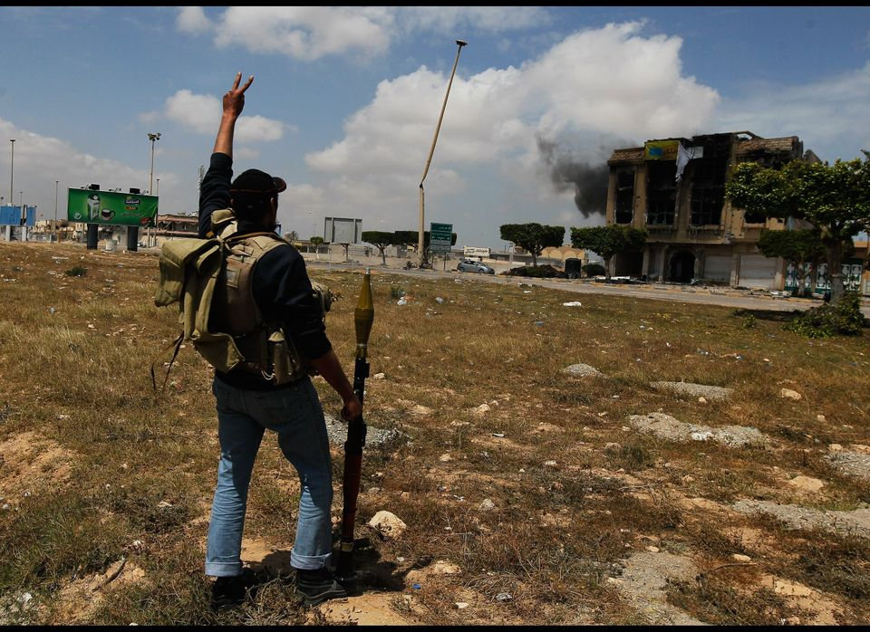 MISURATA, LIBYA - APRIL 20:  A Libyan rebel fighter celebrates as comrades fire on government loyalist troops who refused to