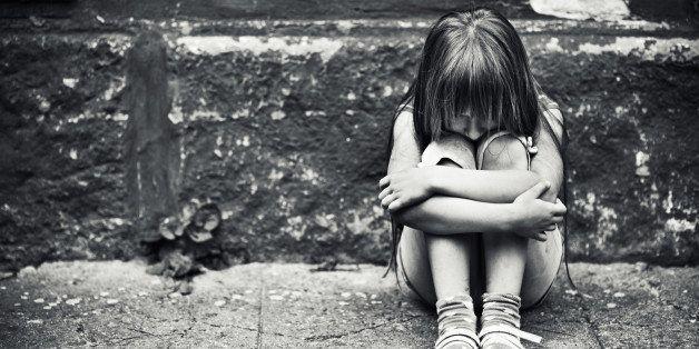 Depressed child sitting at weargered sidewalk. Fine noise applied.