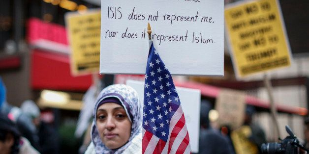 A Muslim woman holds a poster during a protest  against Donald Trump on December 20, 2015 in New York. Republican presidentia