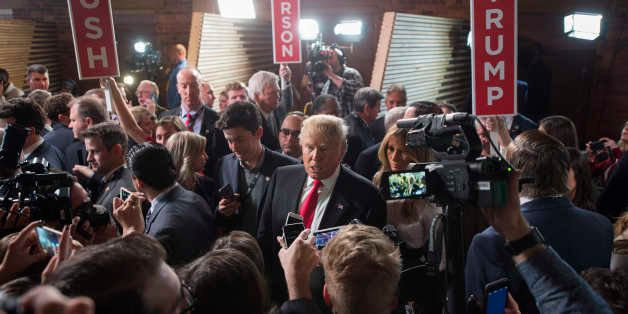 Republican presidential candidate Donald Trump talks with reporters in the Spin Room following the CBS News Republican Presid