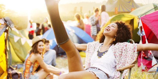 Carefree woman outside tents at music festival