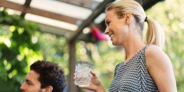 Happy woman holding glass while standing by friend at log cabin during summer party
