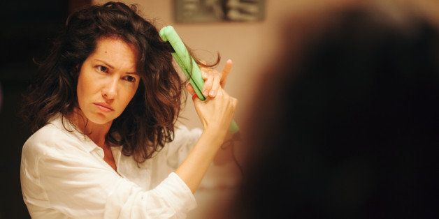 Disappointed woman using hair straightener in bathroom in front of mirror.