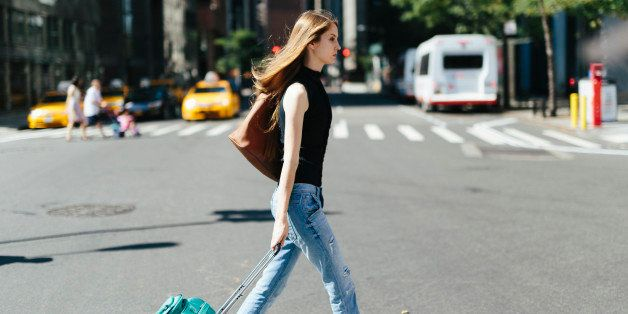 USA, New York City, young woman with rolling suitcase crossing a street