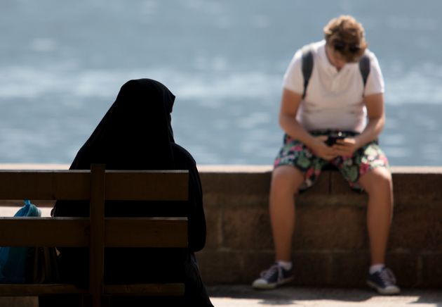 Une femme en niqab, assise sur un banc devant le lac de Zell am See, le 6 août 2018 en