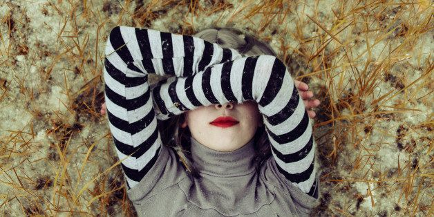 Young woman hidding her face with her arms
