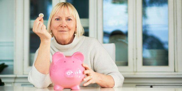 portrait of happy caucasian senior woman saving euro coin into piggybank and smiling at camera