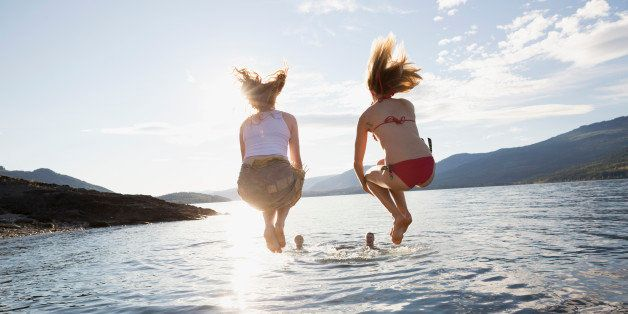 Young women jumping from dock into lake