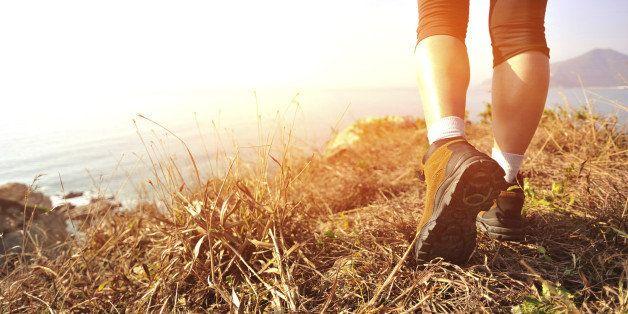 hiking feet walking on seaside mountain peak